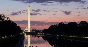 Washington Monument and U.S. Capitol behind reflecting pool at dusk.
