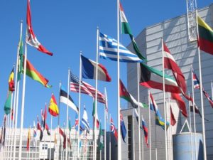 A group of flags from different countries wave in front of a white building and blue sky.