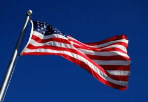 An American flag waves in the wind in front of a blue sky