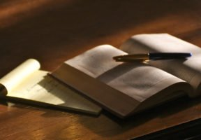 An open book with a pen on top of it lays on top of a notepad on wooden table.