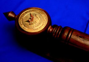 Wooden mace with golden IWP seal on it sits on top of a blue cloth.