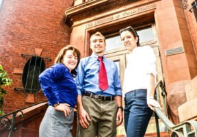 Three IWP students, a woman in a blue shirt and grey skirt, a man in a blue shirt, red tie, and brown pants, and a woman in a white shirt and black pants, stand on the steps outside the Marlatt Mansion