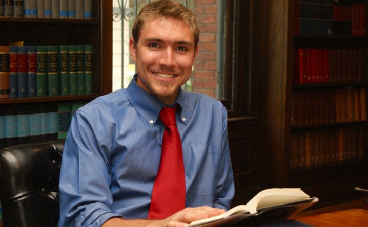 IWP student in a blue shirt and red tie smiles with an open book in his hands. He sits in a black chair at a conference table in front of a bookshelf and window.