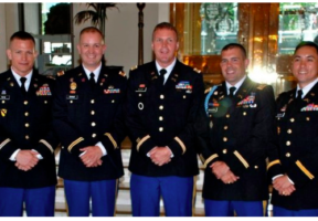 5 military officers stand in uniform.