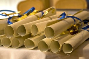 A stack of rolled up diplomas, each tied with blue and gold ribbons.