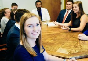 Emily Hertz, a 2017 IWP intern, is shown smiling in a blue dress at a conference table with her fellow interns. The other interns are engaging in conversation with one another.