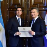Ambassador Federico Gonzalez stands at a diplomatic meeting with an official from another country holding a document in front of two flags.