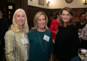 Three women stand for a picture at an IWP event. From left to right: Karen Armstrong wears a green striped blazer, Jackie Wieland wears a blue shirt, and a woman who does not have a name tag wears a black shirt.
