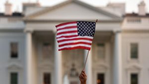 A hand waves the American flag in front of the White House. The American flag is focused on, while the White House is blurred.