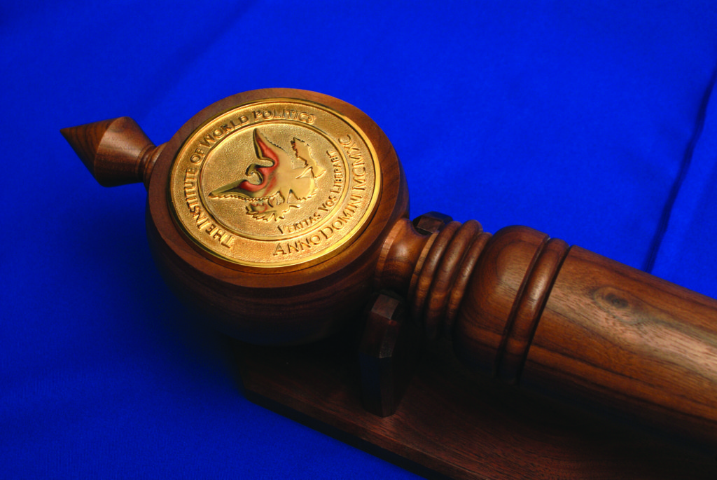 A wooden mace with a golden IWP seal on top of a blue cloth.