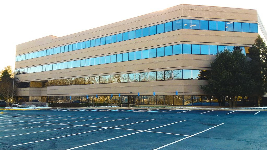 The IWP campus in Reston, Virginia is shown from the parking lot. It is a four story office building with trees to both of its sides.