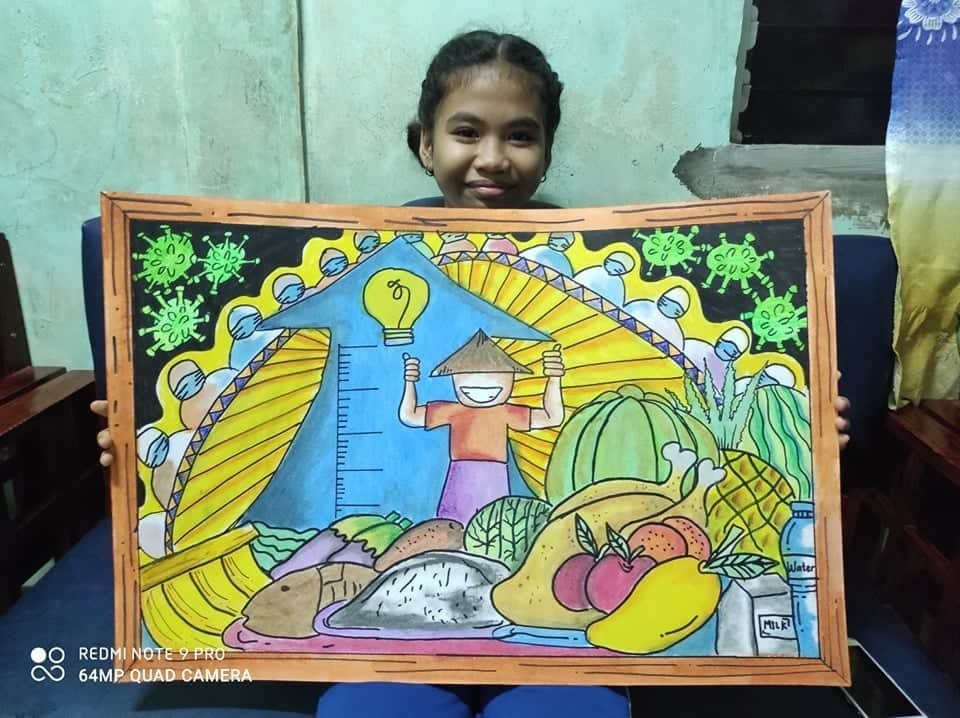 "Girl from an AAI school holding a ""Nutrition to Stop Covid"" poster"