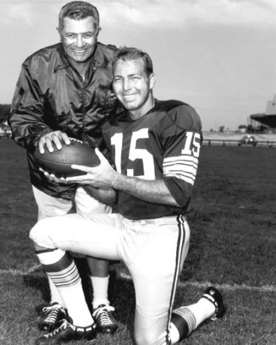 Vince Lombardi (left) and Packers quarterback Bart Starr pose together holding a football.