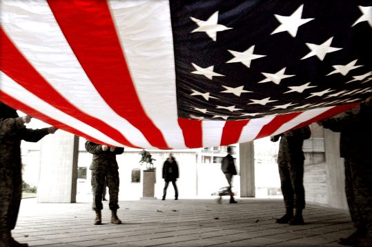 Soldiers preparing to fold an American flag -
