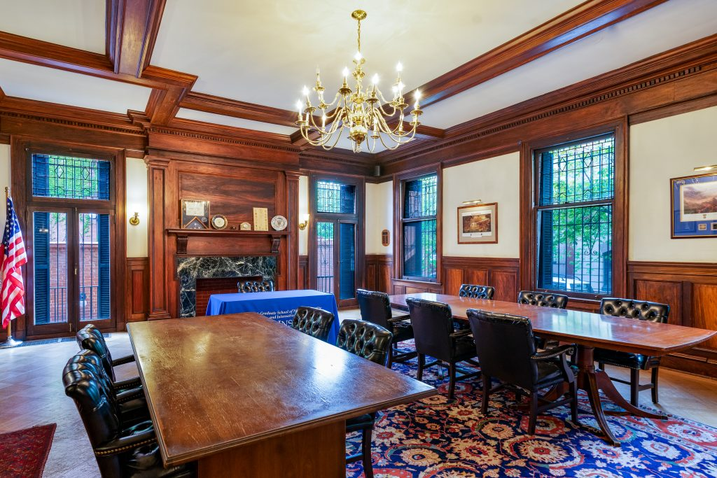 Back Classroom in Marlatt Mansion is pictured. Two conference tables lined with black chairs are shown on top of a blue floral rug. There is a fireplace and two double glass doors. There are paintings and wood paneling on the wall. There are wooden beams on the ceiling and a chandelier hangs from the center.