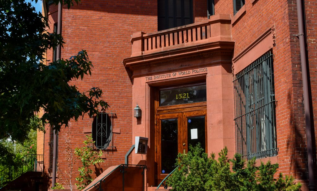 """Front Entrance of Marlatt Mansion on a sunny day. Brick building with double wooden doors and a balcony on second level. Above the doors says """"1321"""" and """"The Institute of World Politics."""""""