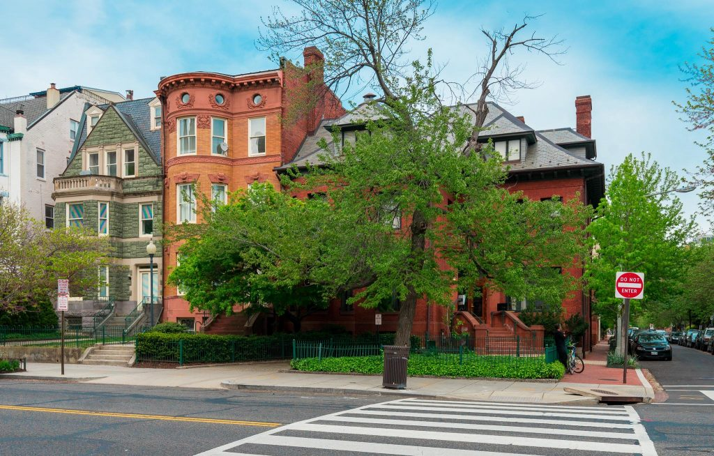 The Washington, D.C. IWP campus is seen from the street. The Bently Building is to the left and the Marlatt Mansion is to the right. A tree covers most of the Marlatt Mansion.