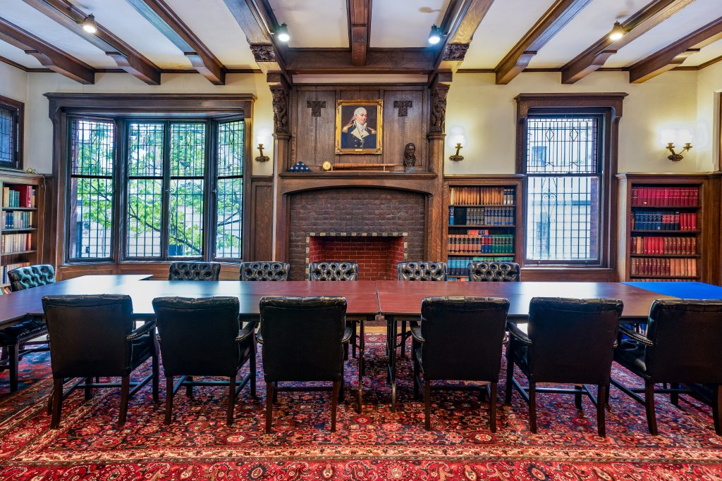 Commodore John Barry Room is seen from a wide angle. A t-shaped conference table surrounded by black chairs on top of red rug is in the center of the room. The last chair has a blue table cloth and IWP banner with American flag behind it. Behind the table is a fireplace with painting on top of it and windows and bookcases on the walls. The ceiling is lined with wooden panels.